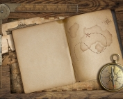 Vintage treasure map in open book with compass and old ruler. Adventure and travel concept.